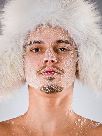 Young man in fur cap with face covered with hoarfrost