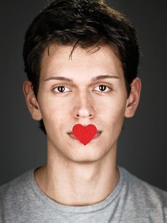 pensiveness: giovane con piccolo cuore rosso sulle labbra