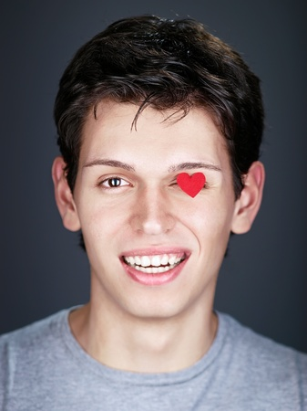 smiling man with small red heart on eye Stock Photo - 8785605