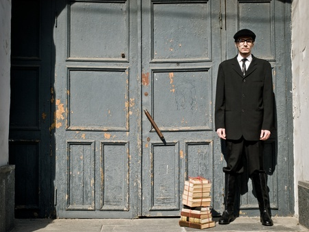 young man in vintage style is standing against the old door Stock Photo