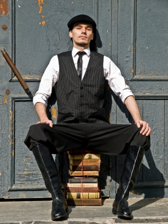 young man is sitting on the sheaf of books in vintage style