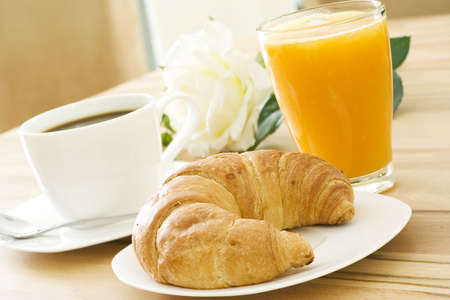 croissants: Croissant, coffee and fruit juice at breakfast Stock Photo