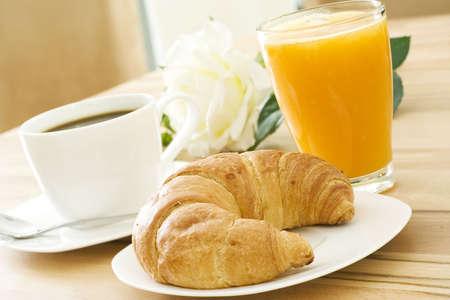 jus orange glazen: Croissant, koffie en fruitsap bij het ontbijt Stockfoto