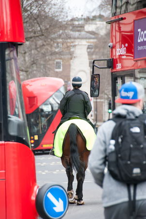 doubledecker: London, England. 06 march, 2016. Bobbies on horseback on the street between the traditional double-decker bus