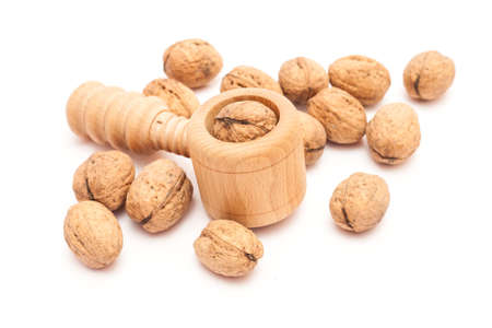 Wooden nutcracker isolated with several walnuts.