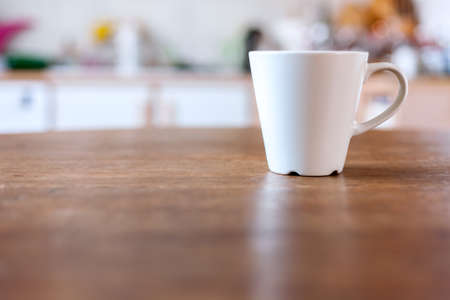 taza de t�: Taza de caf� con el fondo de la cocina de la vendimia de desenfocado. Foto de archivo