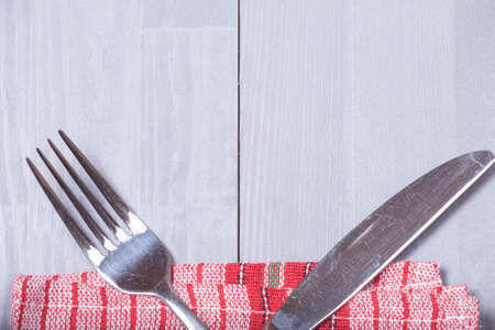 vintage cutlery: Retro old vintage cutlery knife fork natural wooden background kitchen red cloth Stock Photo