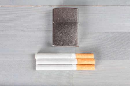 Vintage retro scratched lighter natural wooden grey brown light background cigarettes