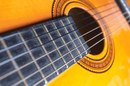 soundboard: Strings, rose and soundboard of a yellow and orange guitar. Musical instrument.