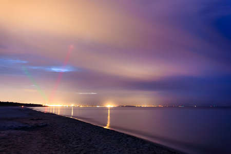Cityscape with sea and laser green and red lights. Colorful sky with clouds. Calm, tranquil scenery.