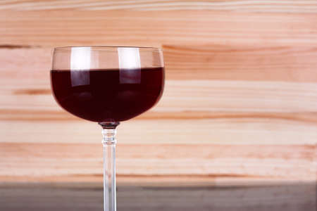 Glass of wine on natural wooden background. Copy space to the right.