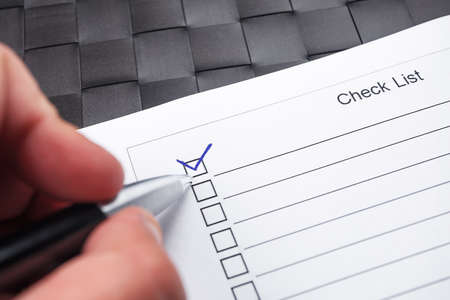mark pen: Checklist with hand doing tick mark with a pen on checkered black background.