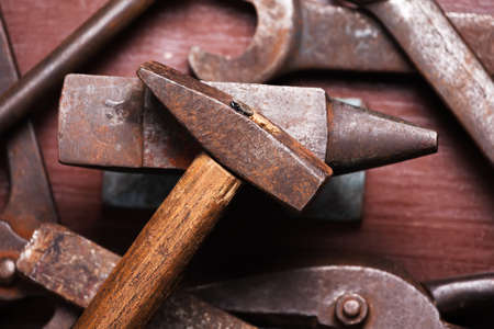 Old rusty rugged anvil, hammer other blacksmith tools on brown natural wooden background. Flat lay top view. Stock Photo