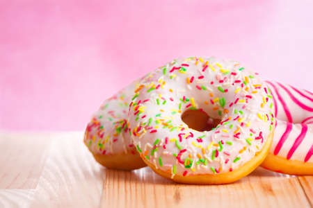 Colorful donuts on natural wooden table and pink background. Copy space to the left.