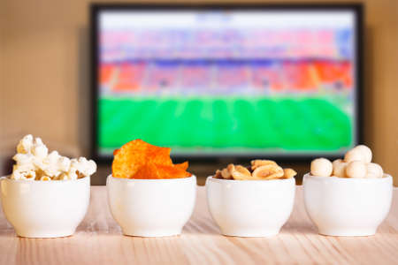 Small bowls of snacks - popcorn, crisps, nuts, candy on natural wooden table. Concept of watching soccer (football) game.
