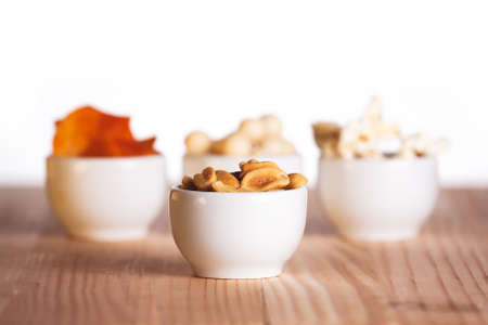 Four small bowls of snacks - crisps, popcorn, nuts and candy on natural wooden table.