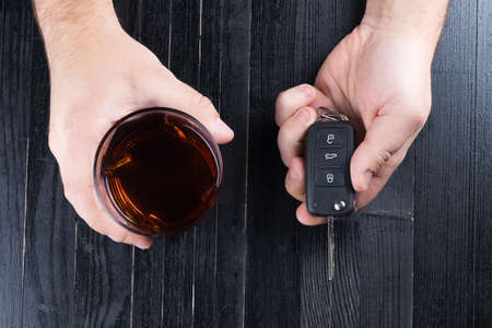drunk test: Car key and whiskey alcohol drink in a glass on black wooden table. Dont drink and drive abstract concept. Stock Photo