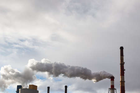 tall chimney: Smoke or steam coming out slowly of tall factory or power plant chimney. Stock Photo