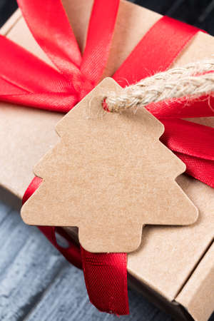 Pine tree label with twine attached on paper present with red ribbon bow. Black natural wooden table. Christmas gift abstract concept.