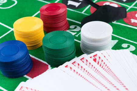 Casino chips and pile of cards on green table. Gambling problems abstract concept. Stock Photo