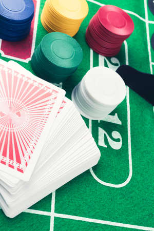 Casino chips and pile of cards on green table. Gambling problems abstract concept. Vintage colors. Stock Photo