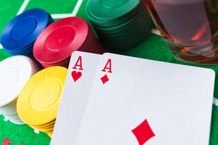 aces: Casino chips and cards on green table. Two aces. Whisky alcoholic drink. Gambling problems abstract concept. Stock Photo