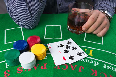 Casino chips and cards on green table. Weak cards three and seven. Elegant business man with whisky alcoholic drink. Gambling problems abstract concept. Stock Photo
