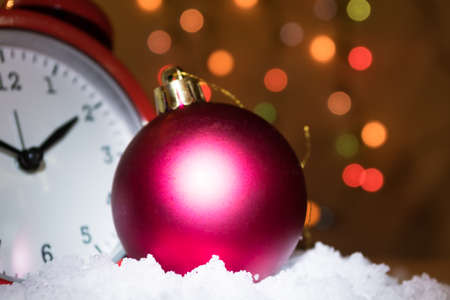 corner clock: Christmas tree bauble ornament on the snow. Red vintage clock. Colorful tree lights bokeh background. Copy space ath the top right corner. Time of celebration abstract concept.