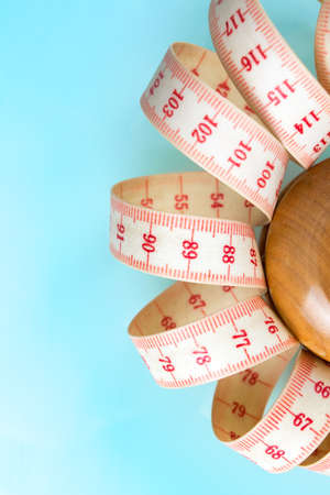 Yo-yo effect in diet concept. Wooden yoyo with centimeter measure. Vertical orientation. Blue pastel background. Copy space on the left. Stock Photo