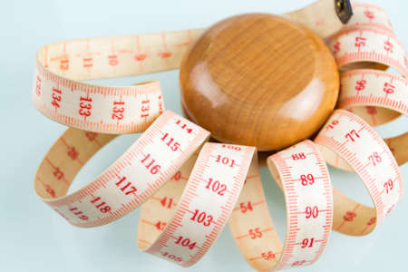 Yo-yo effect in diet concept. Wooden yoyo with centimeter measure. Reflective glass background. Stock Photo