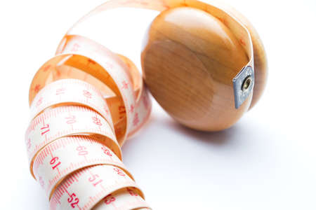 Yo-yo effect in diet concept. Wooden yoyo with centimeter measure. Isolated on white background.