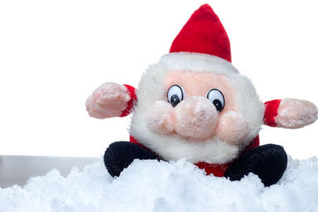Funny christmas santa claus red and black mascot. Sitting on a snow. White isolated background. Copy space on the left. Stock Photo
