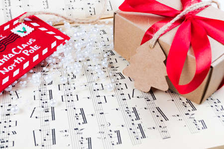 Christmas gift or present with label and twine on music sheet. Red ribbon bow. Notes. Letter to santa claus of the north pole.