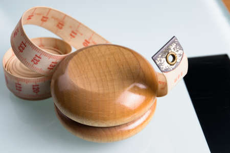 Yo-yo effect in diet concept. Wooden yoyo with centimeter measure. Bathroom weight scale.