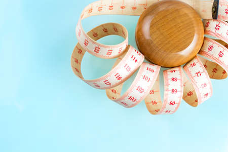 Yo-yo effet dans le concept de régime. Yoyo en bois avec mesure centimétrique. Fond pastel bleu Copiez l'espace dans le coin inférieur gauche. Banque d'images - 66319319