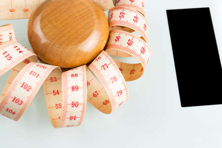 Yo-yo effect in diet concept. Wooden yoyo with centimeter measure. Bathroom weight scale with black screen display. Stock Photo