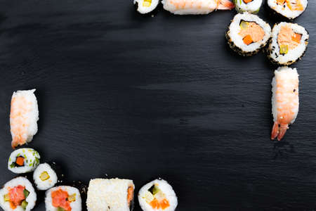 Japanese sushi on black kitchen slate plate. Typical asian cuisine. Maki and nigiri. Frame. Copy space in the center.