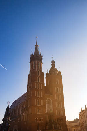 St. Marys Basilica on a main square in Krakow, Poland. Warm sunset light. Blue sky. Stock Photo