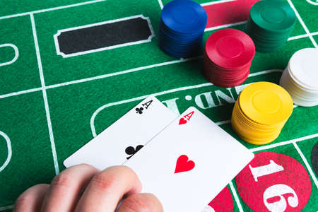 casino table: Two aces with chips on green casino table. Gambling and winning abstract concept. Copy space in the top left corner.