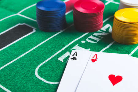 Two aces with chips on green casino table. Gambling and winning abstract concept. Angle view. Copy space on the left. Stock Photo