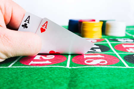 Two aces with chips on green casino table. Gambling and winning abstract concept. Man hand.