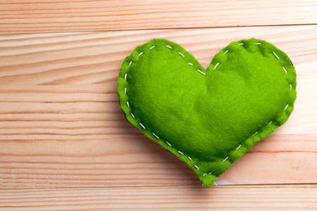 Green heart on natural wooden table on Valentines Day. Pantone greenery color theme. Copy space on the left. Stock Photo