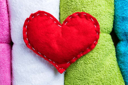 massage symbol: Red homemade heart on colorful towels on Valentines Day. Romantic spa abstract concept. Stock Photo