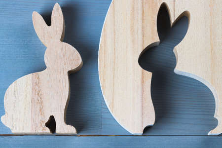 Spring easter bunny figurine on natural grey wooden background. Flat lay top view.