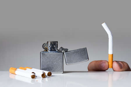 quiting: Young man holding broken cigarette. Quiting nicotine and tobacco addiction abstract concept. Copy space on the top.
