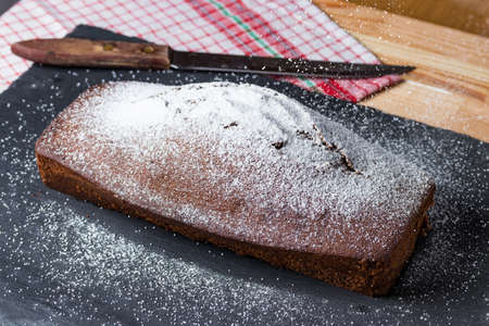 Homemade baked sweet gingerbread on a slate plate with old kitchen towel, knife and powdered sugar. Vintage or retro look.
