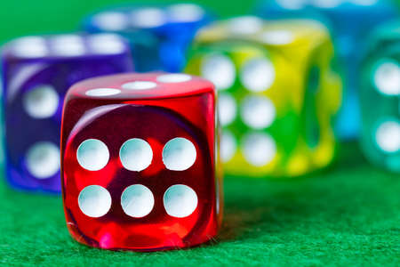 Colorful dice on a green casino background. Shallow depth of field.