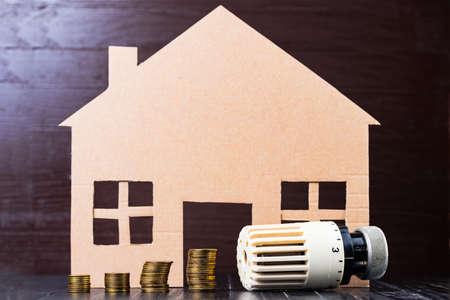 housebuilding: Home heat savings or expenses concept. Coin stacks, radiator regulator, house shape.