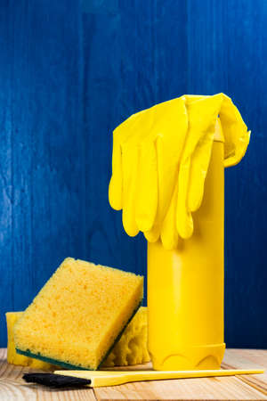 Yellow cleaning supplies on a blue background. Vertical orientation. Stock Photo