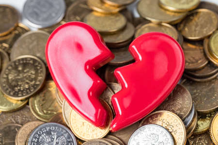 Broken red Valentines Day heart on a pile of coins. Love and money problems abstract concept. Stock Photo
